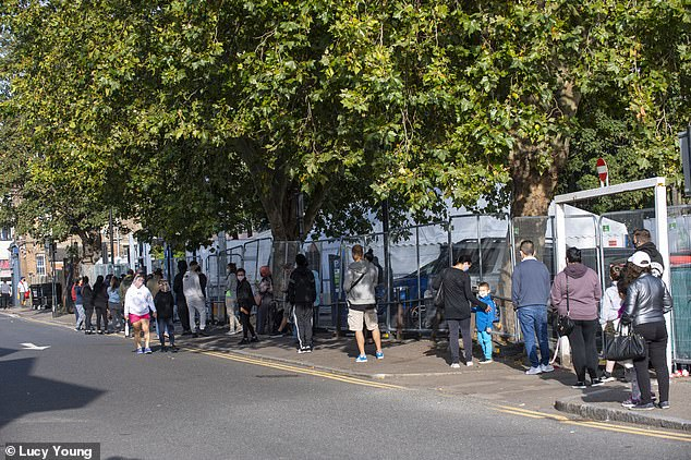 Members of the public are pictured queuing outside a coronavirus testing centre in Edmonton, North London, as people across the country say they are struggling to get hold of tests