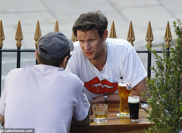 Catching up: Matt Smith put on a casual display in a white logo t-shirt as he enjoyed an outing with a group of friends at a pub in London on Sunday