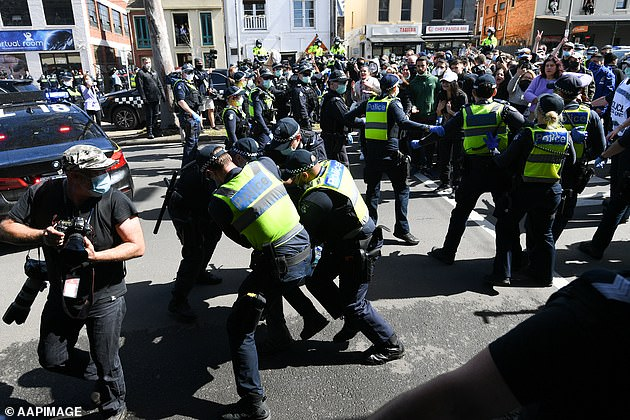 Pictured: Police scuffle with protesters during an anti-lockdown protest in Melbourne on Sunday September 13