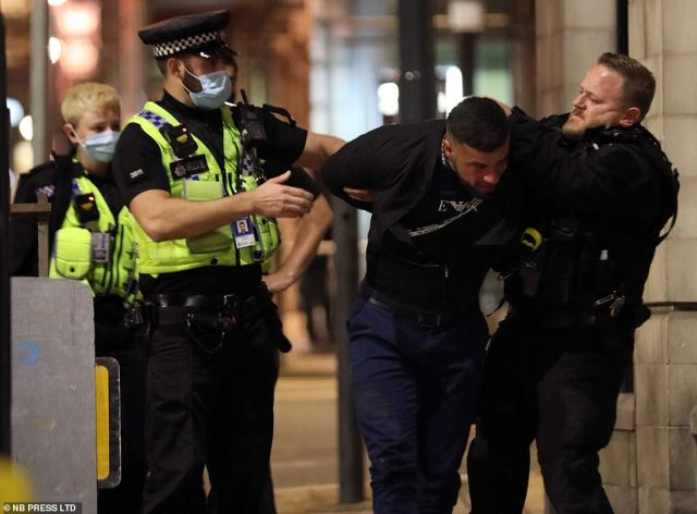Police officers, two pictured wearing masks, appear to restrain a man in Leeds city centre on Friday night