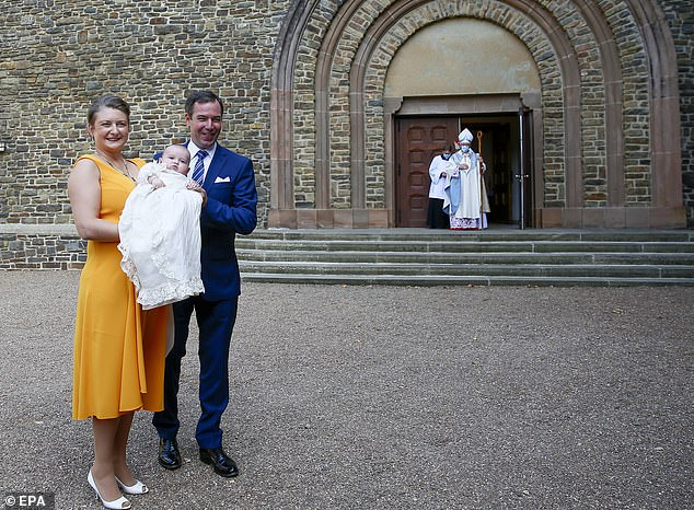 New mother Stéphanie donned an orange dress and white heels to the ceremony, while she tied her blonde hair back. Meanwhile, Prince Guillaume, Hereditary Grand Duke of Luxembourg and heir assumptive to the throne, opted for a navy blue suit and white shirt, with a powder blue tie and pocket square for his son's big day