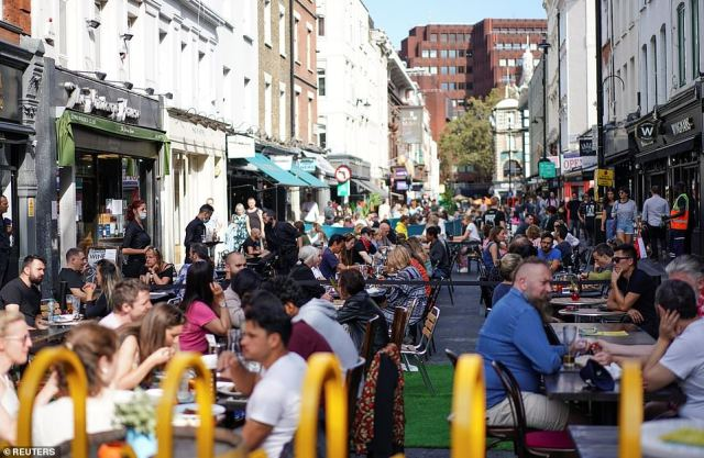 Hundreds of people sit at the tables outside restaurants in Soho, central London, as the Government warns Britain is at a 'tipping point'