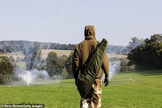A model poses in camouflage utility-inspired clothing as explosions go off in the background and smoke billows across the countryside setting