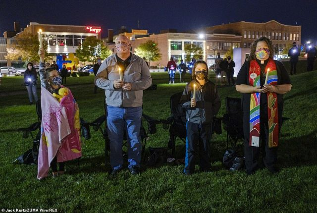 IOWA:A family light candles at a vigil in Poppajohn Sculpture Park in Des Moines where about 200 people gathered in honor of Ginsburg Sunday night