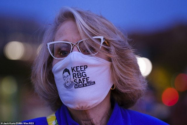 IOWA:A woman wearing her COVID-19 face mask at a vigil for Ginsburg in Poppajohn Sculpture Park