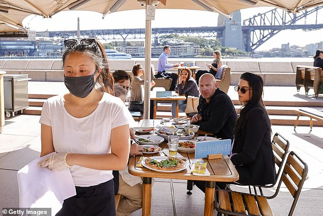 Both of the COVID-19 cases recorded in NSW on Tuesday are in returned travellers in hotel quarantine (pictured workers wear face mask at Opera Bar in Sydney)