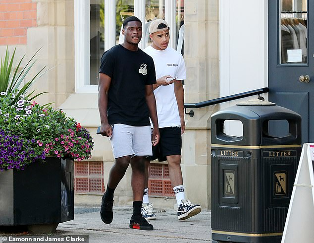 Pals:Greenwood, 18, added to his casual look with a baseball cap and running shoes as he linked up with academy prospect Mengi, also 18, for a day out