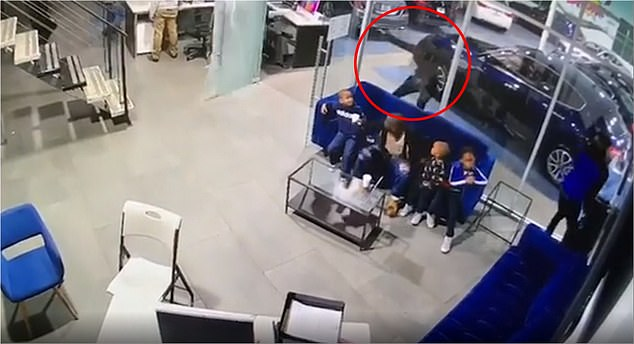 The dad and his children were sitting on a couch inside the used car shop when a man in a black hoodie (circled) ran up and began firing through an open glass door