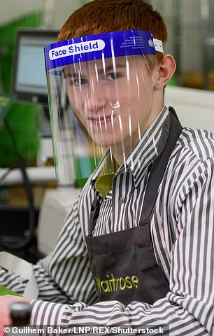 Waitrose employee Fergall, 16, wears a face shield at the same store on April 15