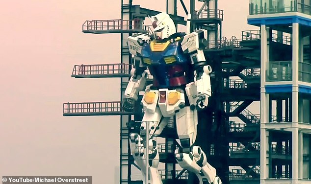 Video footage shows the massive 25 tonne robot moving its right arm and fingers, lifting its legs and kneeling while workers watch from a nearby observation deck