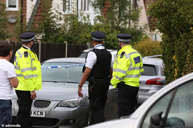 Police officers are seen at the scene after officers were injured in north London today