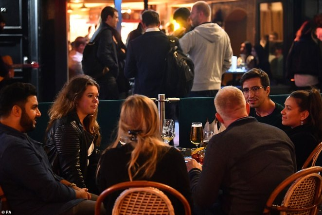 Boris Johnson ordered all pubs and restaurants in England to close at 10pm from Thursday night and made table service mandatory. Pictured, people drinking outside in Soho, London, on Wednesday night