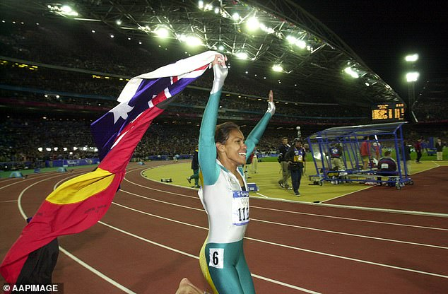 Cathy Freeman walks a lap of honour, carrying the Australian and Aboriginal Flags, after winning Gold in the Womens 400m Final in 2002