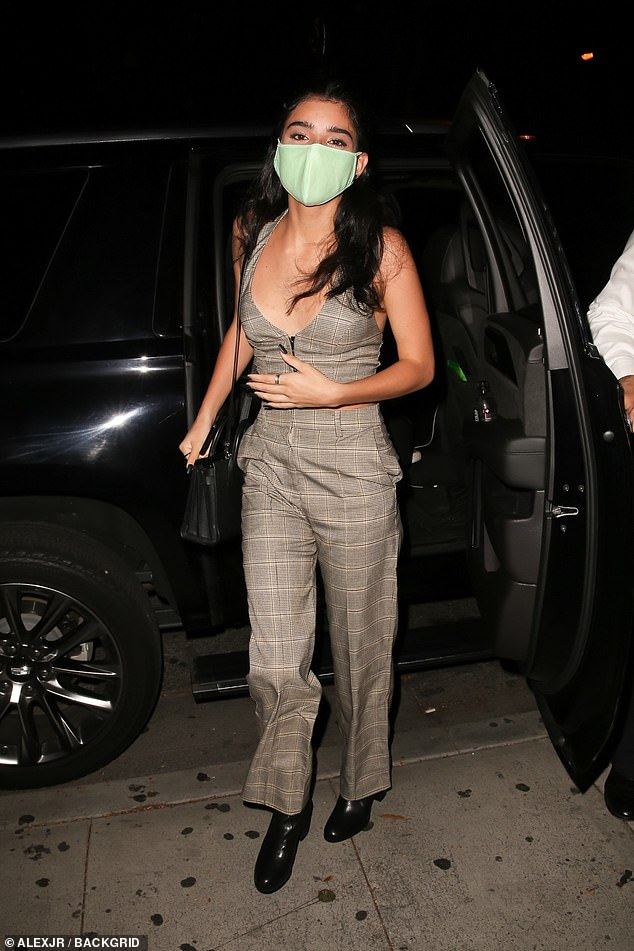 Plaid baby: Charli's older sister Dixie exited their SUV in an all plaid ensemble that included a plunging zip-front crop top and a pair of oversized trousers that slightly flared at the hem
