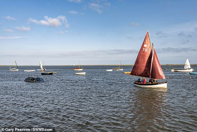 A hapless driver returned to his car to find it almost fully submerged underwater - with sailing boats cruising past it