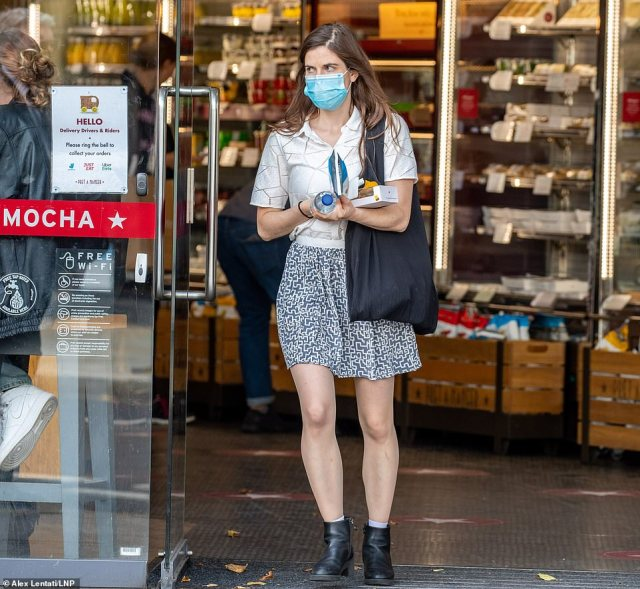 A woman wears a face masks as she stops to buy some food at a branch of Pret A Manger in Chelsea, London