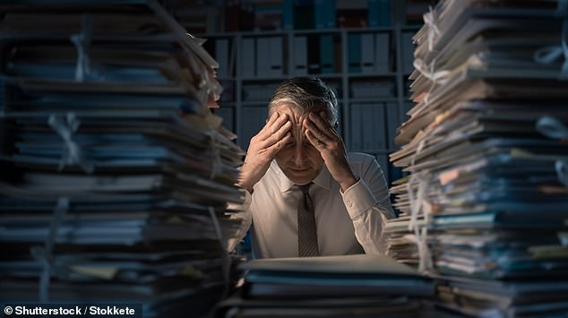 Experts from the US explored why basing one's self-esteem around financial success — the so-called 'Financial Contingency of Self-Worth' — can have drawbacks. Pictured, a man works late in an office surrounded by reams of paperwork