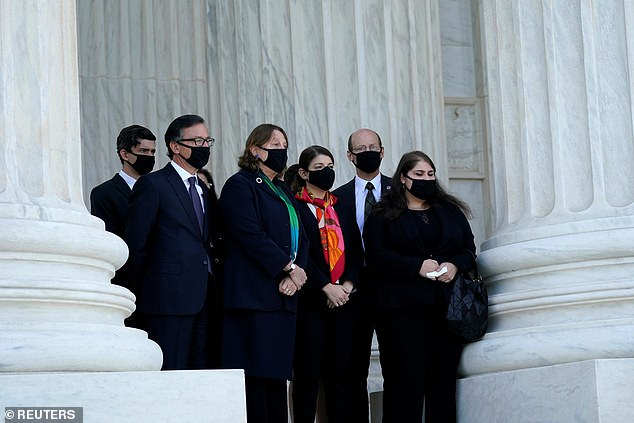 Family members of Justice Ruth Bader - including Jane C. Ginsburg - wait her casket to arrive at the court