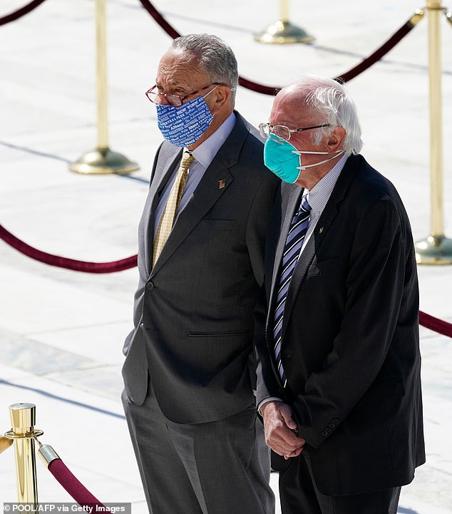 Senate Minority Leader Chuck Schumer (L) and Senator Bernie Sanders pay their respects to Ginsburg