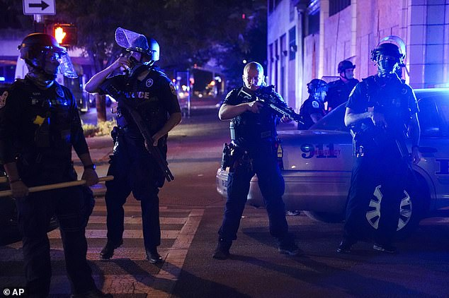 Heavily-armed riot police stand guard in a street in downtown Louisville amid protests sparked by a Kentucky grand jury's decision to clear three officers of charges for killing Taylor