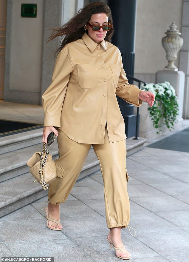 Stepping out: That day Ashley was glimpsed emerging from hotel while modeling a fashion forward ensemble that included a khaki raincoat blouse