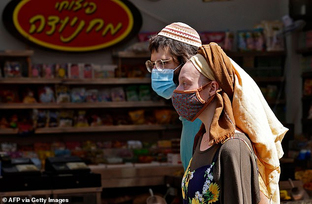 Shoppers, wearing protective masks due to the COVID-19 pandemic, walk at the Mahane Yehuda market in Jerusalem on Thursday ahead of new restrictions for all non-essential businesses