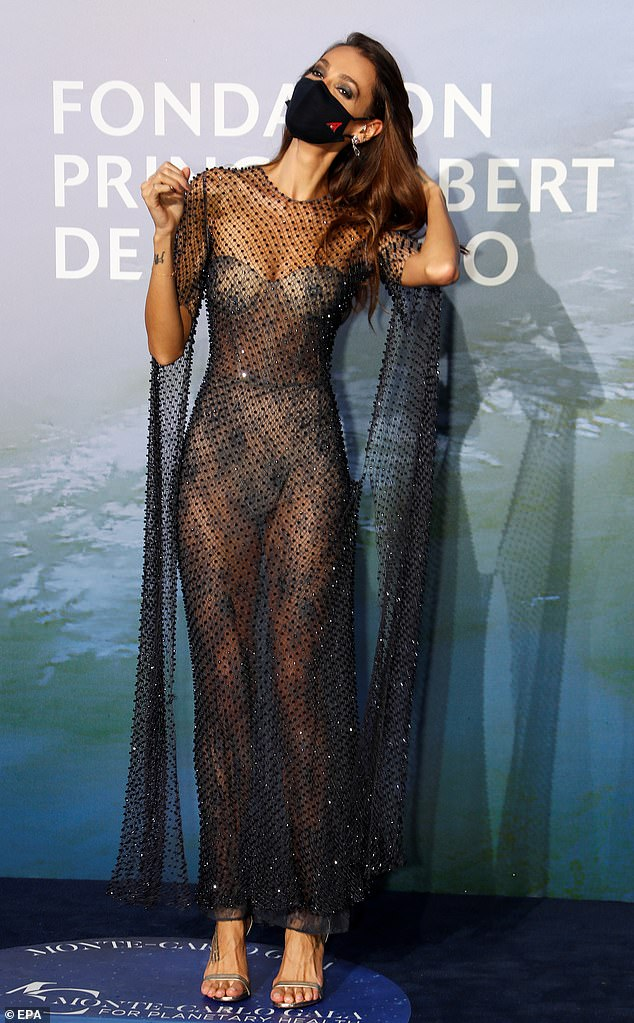 Turning heads:Sofia left little to the imagination in an incredibly sheer black mesh gown covered with silver sequins, teamed with a black mask as she posed on the blue carpet