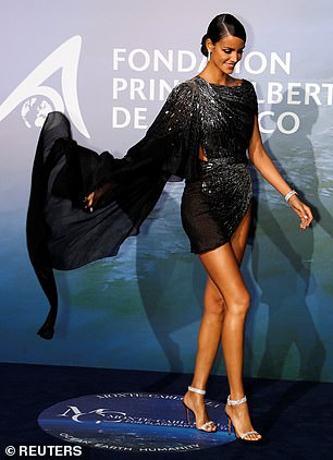 Legs for days: Shehighlighted her endless pins in a dramatic black mini dress with flowing detailing