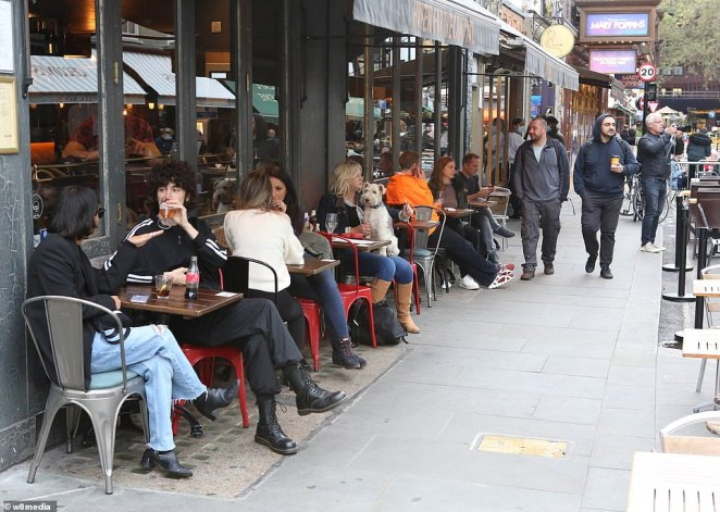 Outside tables in Soho were filled with people making the most of the evening before the pubs and restaurants were closed early to follow the new restrictions
