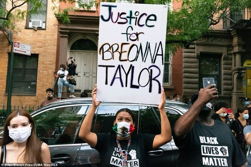 A demonstrator is shown holding a 'Justice for Breonna Taylor' sign on West 15th street during a Black Lives Matter rally against Corey Johnson in New York on Thursday