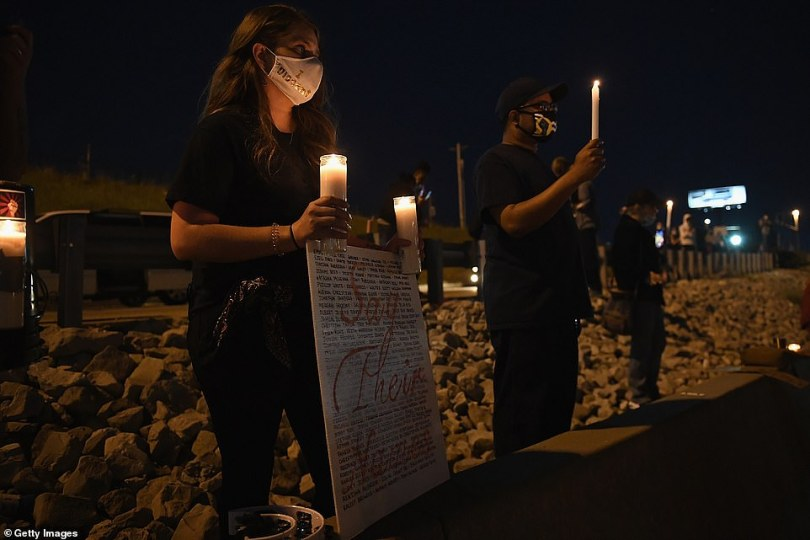 A woman holds a sign and candles during a protest action along Interstate 64 in St. Louis, Missouri, on Thursday