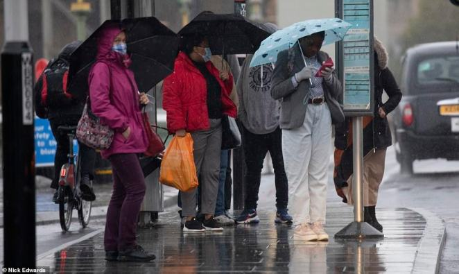 Commuters in Westminster, London, were caught in a downpour on Friday morning as they waited for a bus in the autumn weather
