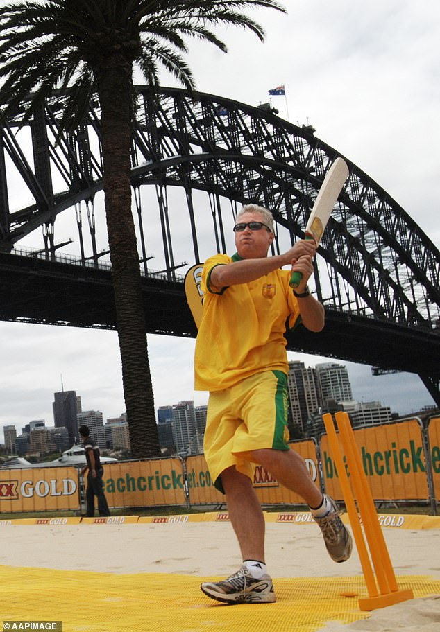 Jones enjoys a game of beach cricket against the backdrop of the Sydney Harbour Bridge in 2006