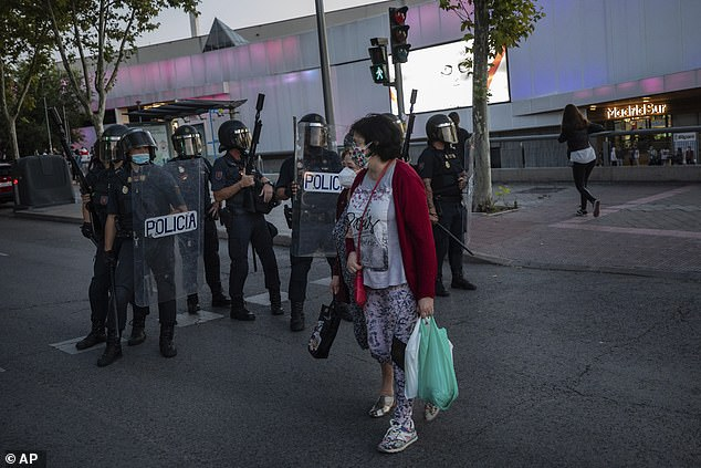 Authorities in Madrid are expanding restrictions on movement to a further eight areas of the Spanish capital, which is leading the country's contagion curve (police enforcing neighbourhood restrictions)