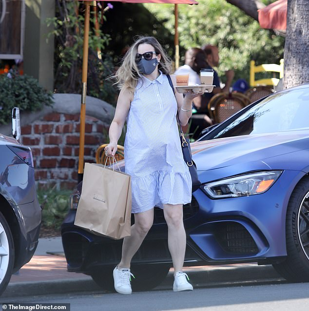 Breakfast run: The expecting mother made sure she and her baby both had room to breathe, throwing on a loose blue and white striped dress with a collar detail as she picked up coffee and food in LA