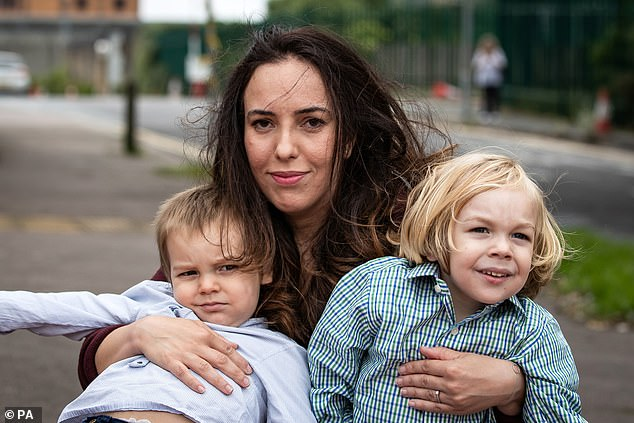 Standing by her man: Lawyer Stella Moris with her two children by Assange