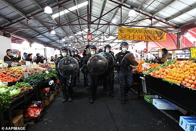 Police move protesters on through the Queen Victoria Market during an anti-lockdown protest in Melbourne, Sunday, September 13, 2020