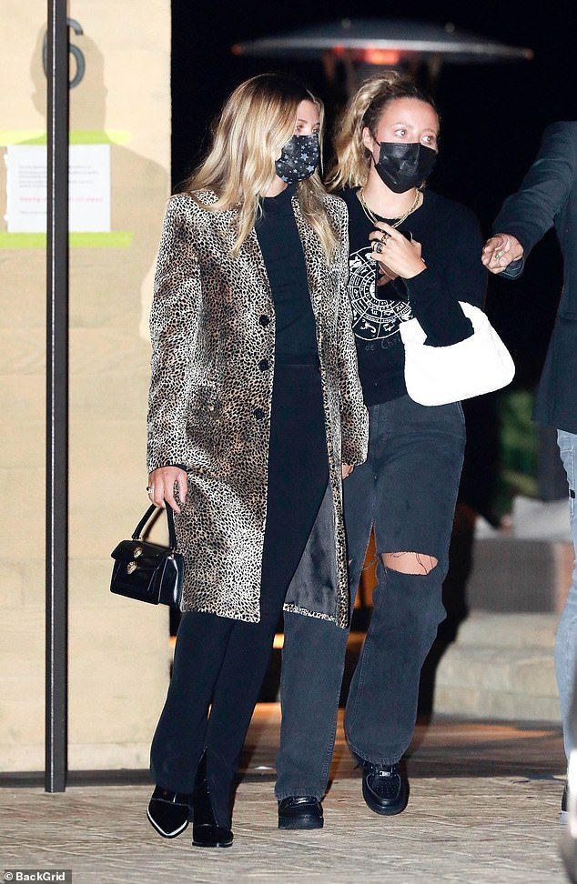 Fashion maven:The daughter of Lionel Richie added a boost to her height with black heeled boots and toted a small designer handbag
