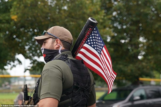 A Proud Boy supporter is seen carrying a bat and an American flag at Saturday's rally. A large counter-protest nearby led to fears of violent clashes between left-wing and right-wing groups