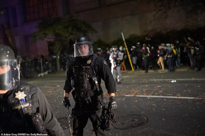 One officer is pictured with his baton ready to swing at any protester that approaches
