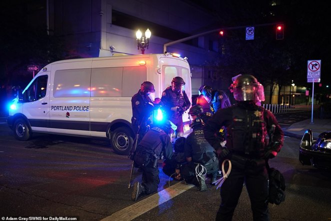 A protestor is arrested by police in Portland during Saturday night's events