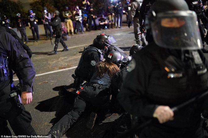A female police officer takes part in the arrest of aBlack Lives Matter supporter