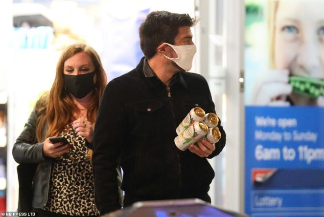 Two people wearing masks are seen after visiting an off-licence following a night out in Leeds city centre