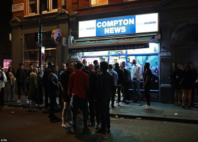People queuing outside Compton News convenience store in Soho, London, after pubs and restaurants were subject to a 10pm curfew