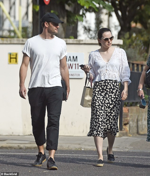 Relaxed: Tom also cut a stylish figure in a white T-shirt and black chino trousers
