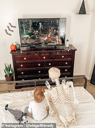 Theo is seen watching television with the skeleton