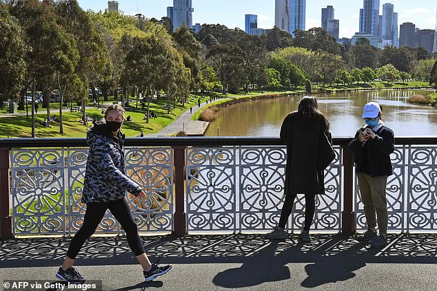 A walker wearing a face mask crosses a bridge over the Yarra River in Melbourne on Sunday