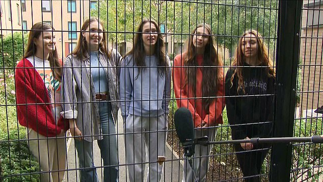 Manchester Metropolitan Students speak behind a fence following an outbreak of the virus