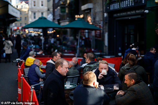 Downing Street is hoping to avoid a nationwide social lockdown as infection rates remain low in the south-west and south-east of the country outside London.  Above, after work drinkers enjoy a pint outside the Market Porter pub in Borough Market