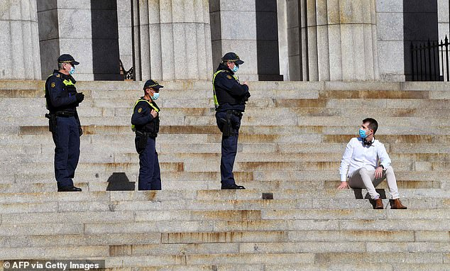 Three armed law enforcement officers are pictured on July 31 at Melbourne's Shrine of Remembrance approaching a man in a face mask